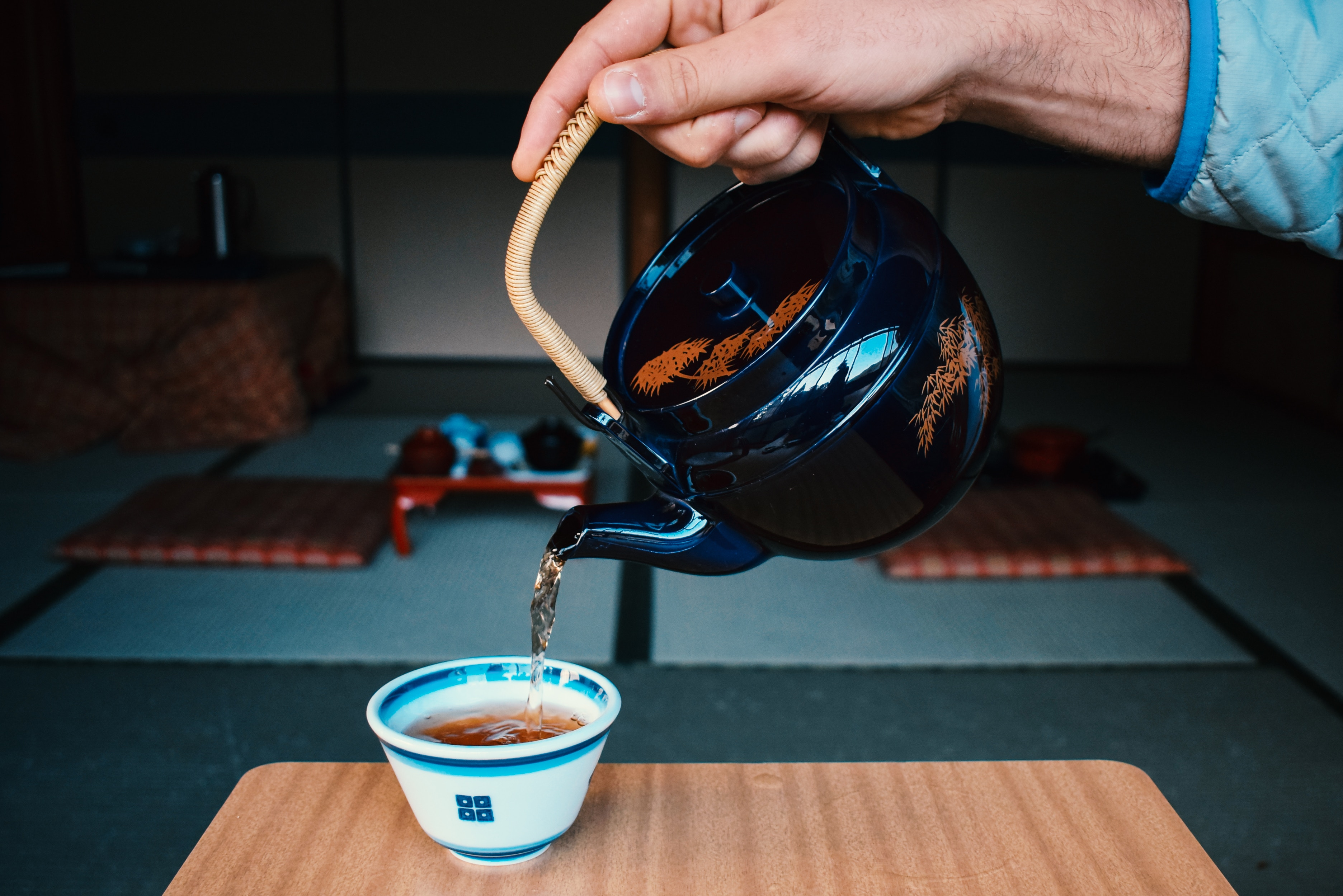 une main verse du thé dans une tasse avec service asiatique conte la tasse de thé conte